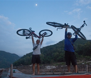 Rit and Sack unloading our bikes from the roof at Pak Beng