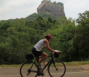 Carel Foster cycles past Sigiriya Rock Fortress
