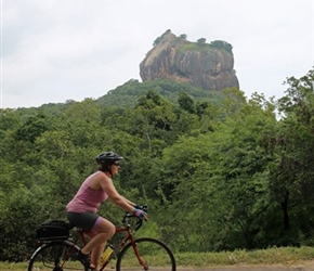 Jo Postlethwaite cycles past Sigiriya Rock Fortress