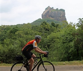 Malc Foster cycles past Sigiriya Rock Fortress