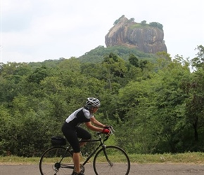 Dianne Young cycles past Sigiriya Rock Fortress