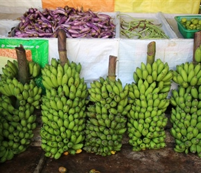 Bunches of green bananas outside a shop