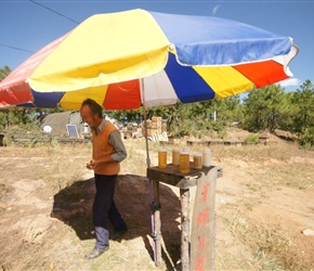 Honey seller with his tent and hives behind