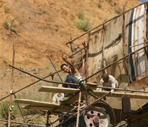Quarry worker waves from a precarious perch