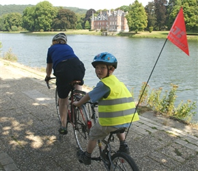 Penny and Oliver cycle pas John Chateau on the River Meuse