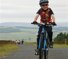 Finlay  arrives at the top of the Ros Castle climb